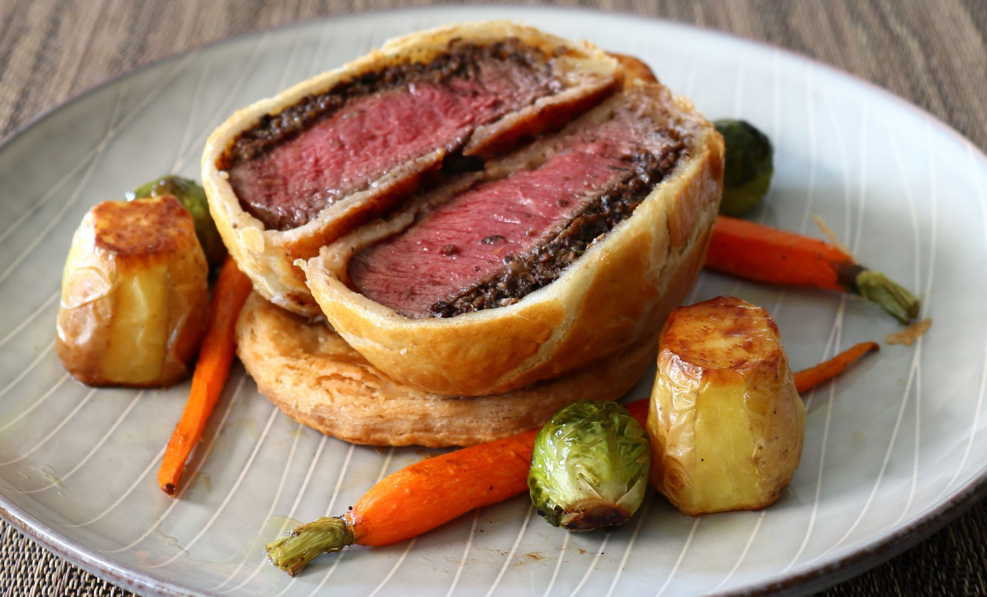 a mini beef Wellington sliced open to show the juicy-looking pink interior, on a plate with fondant potatoes, roasted Brussels sprouts, and carrots