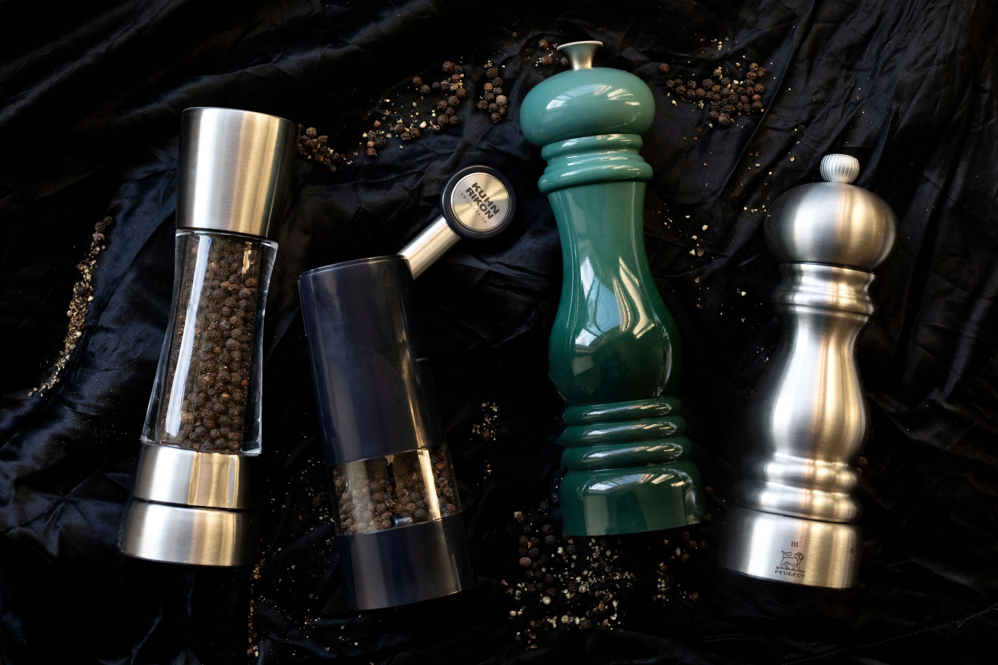 Four pepper grinders on black sheet with loose peppercorn