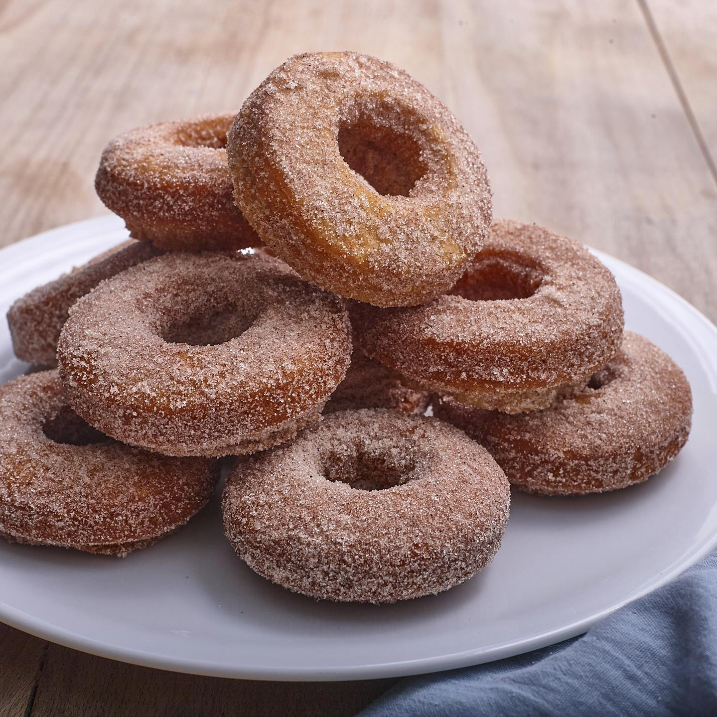 A pile of sugared donuts on a white plate with a blue napkin tucked underneath.