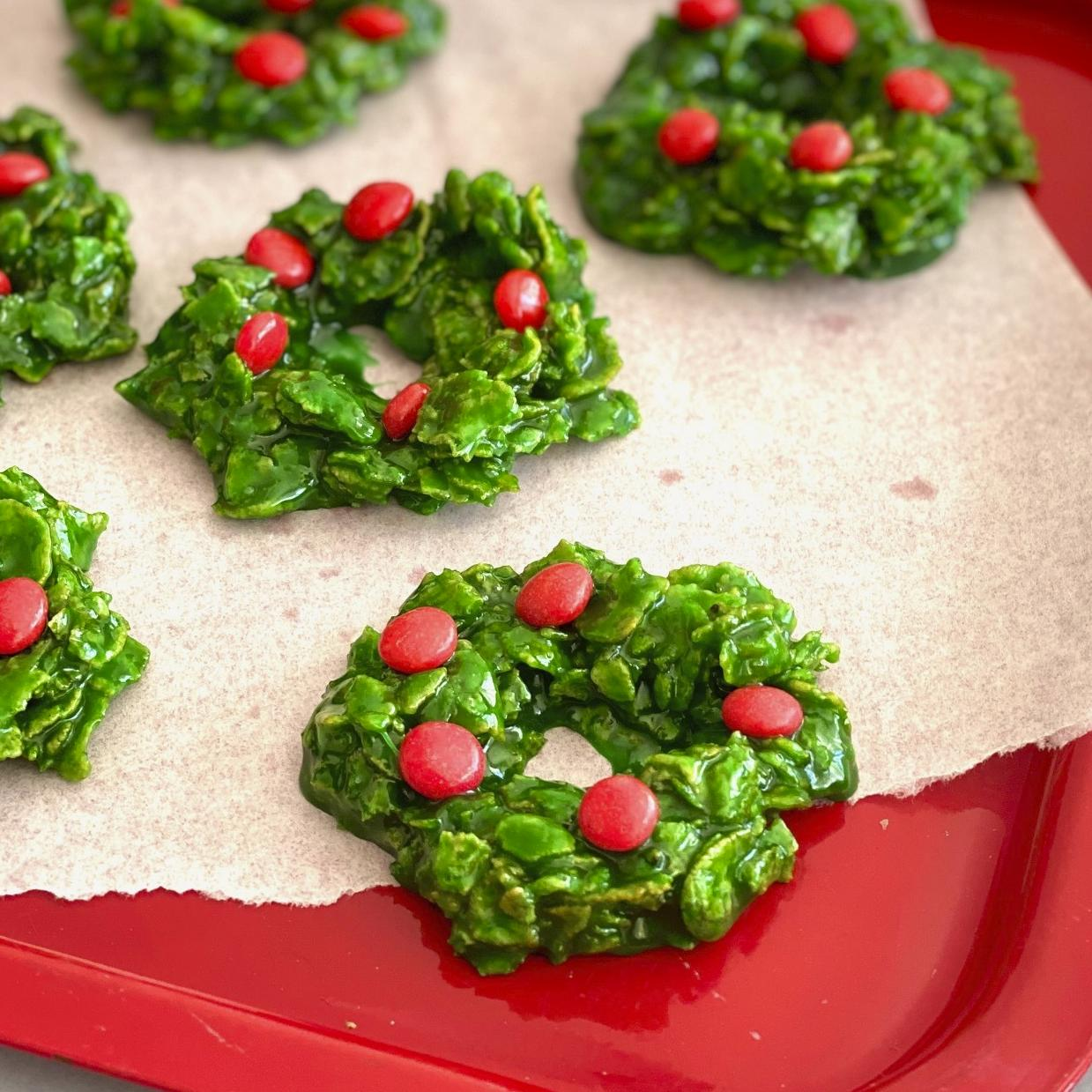 Six Christmas wreath cookies on a red tray.