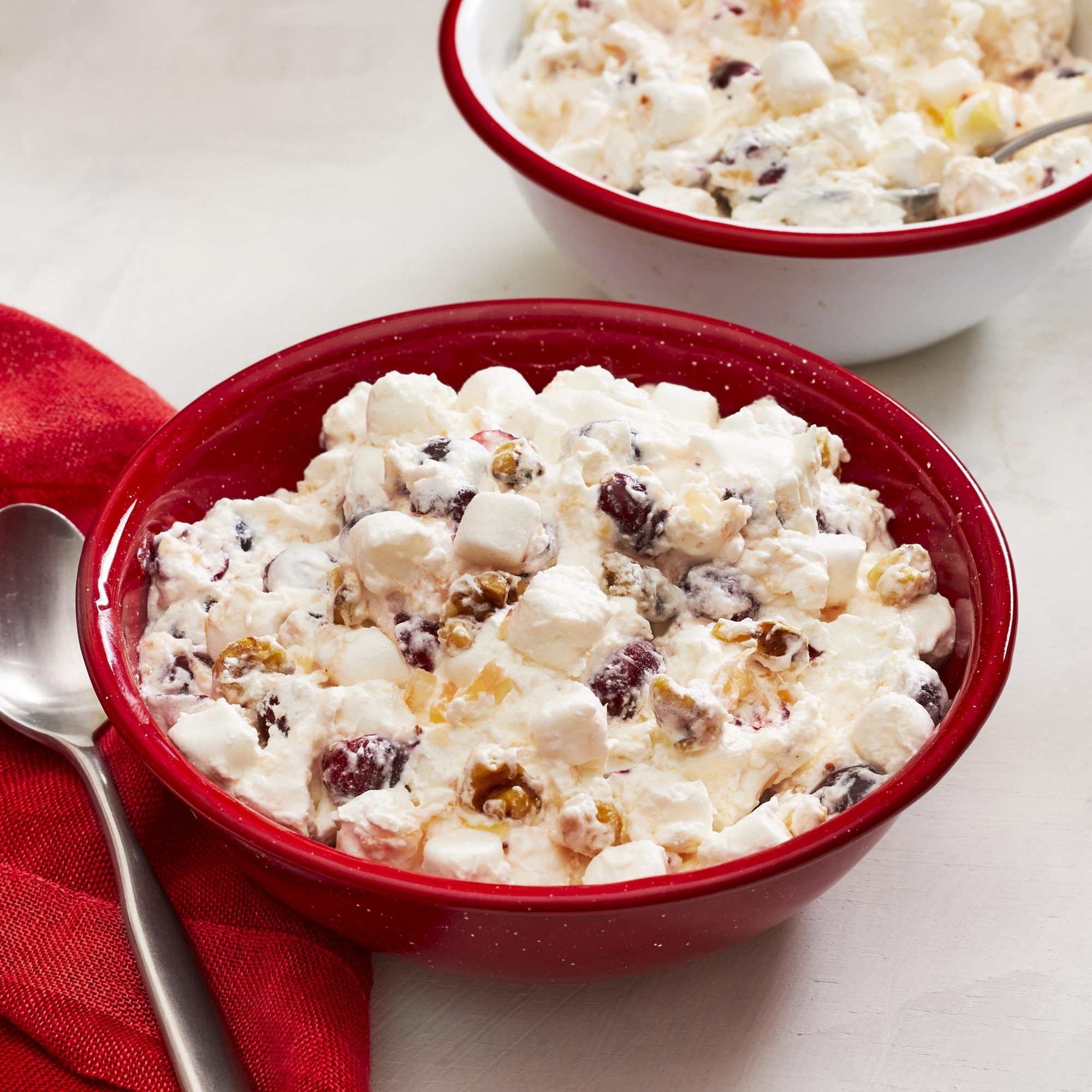 Two bowls of cranberry fluff, a red napkin, and a silver spoon.