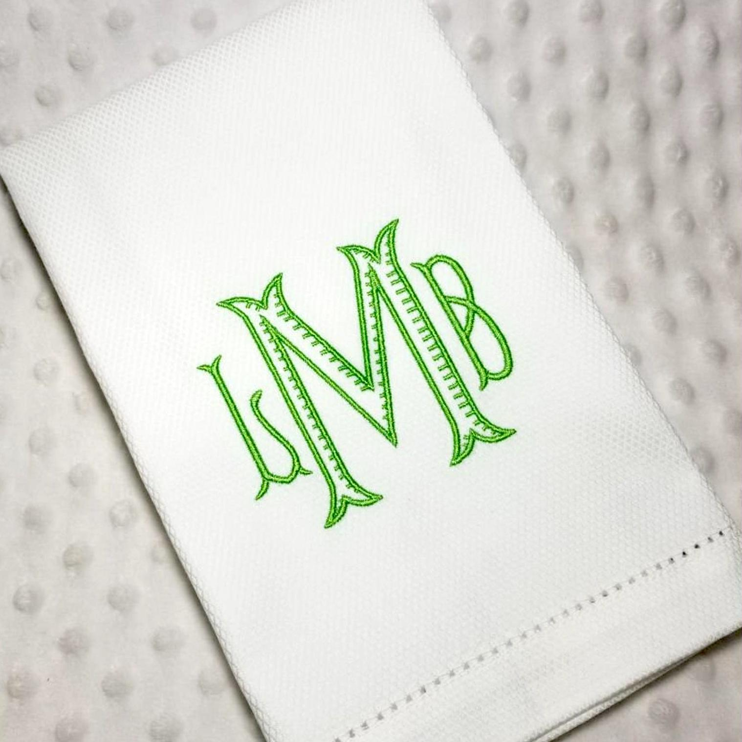 white hand towel with initials monogramed in green font