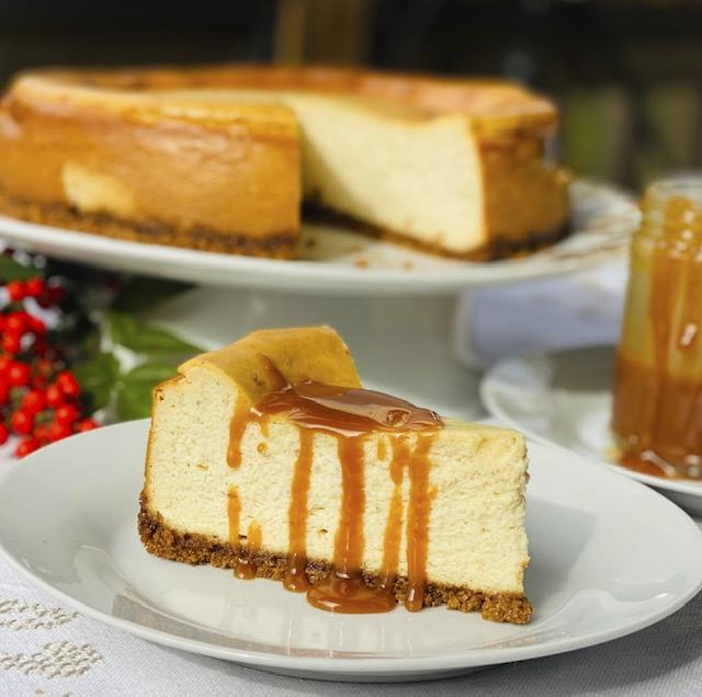 Slice of cheesecake with caramel drizzle. The remaining cheesecake is in the background.