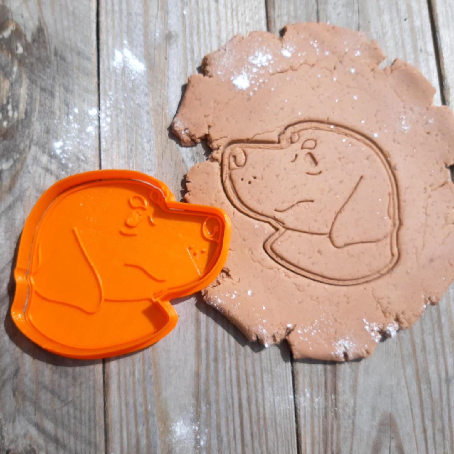 dog cookie cutter and dough pressed with cookie cutter stamp