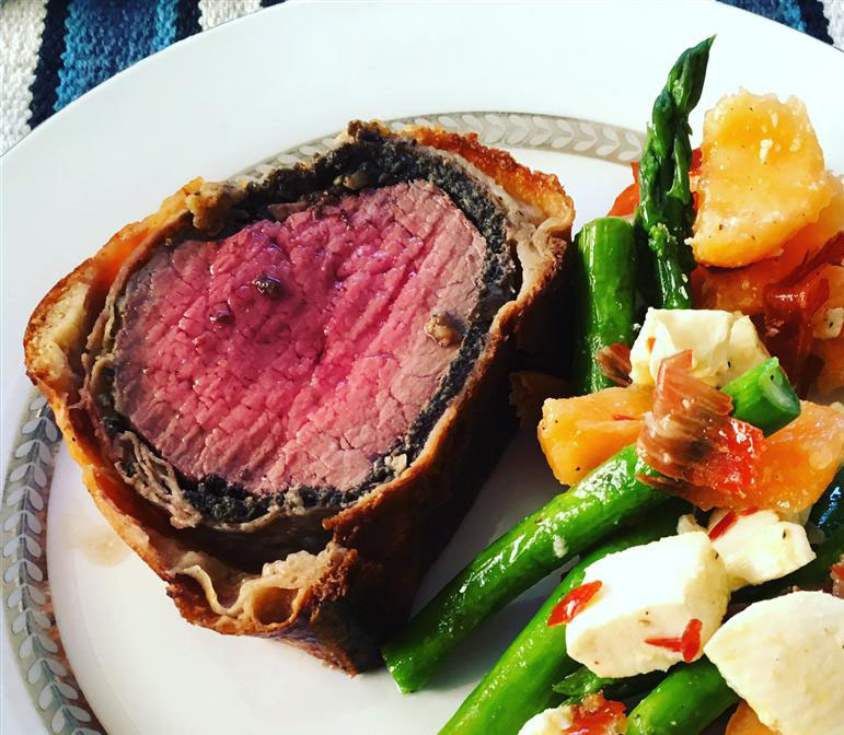 a slice of juicy-looking beef Wellington cooked medium rare on a white china plate with mixed vegetables on the side