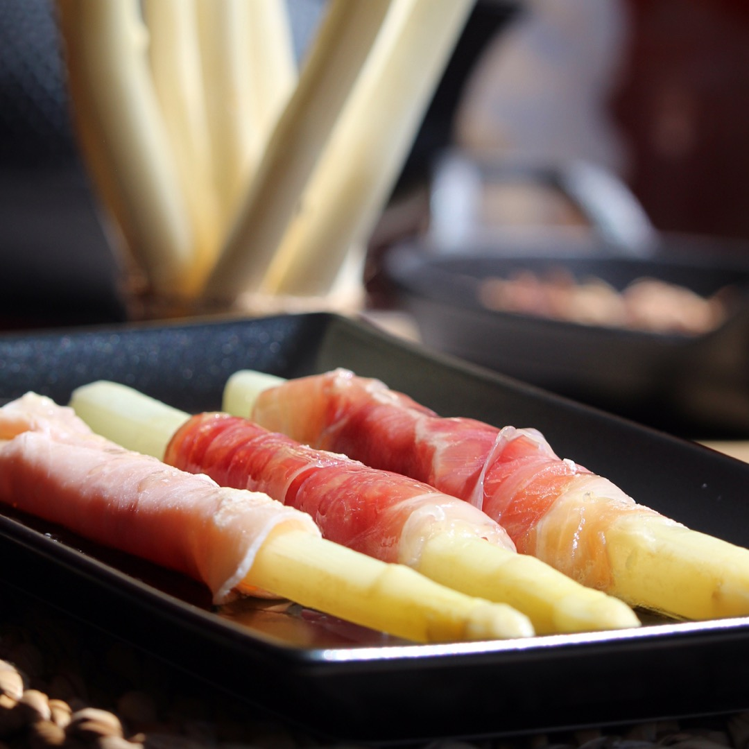 white asparagus wrapped in ham on a dark plate