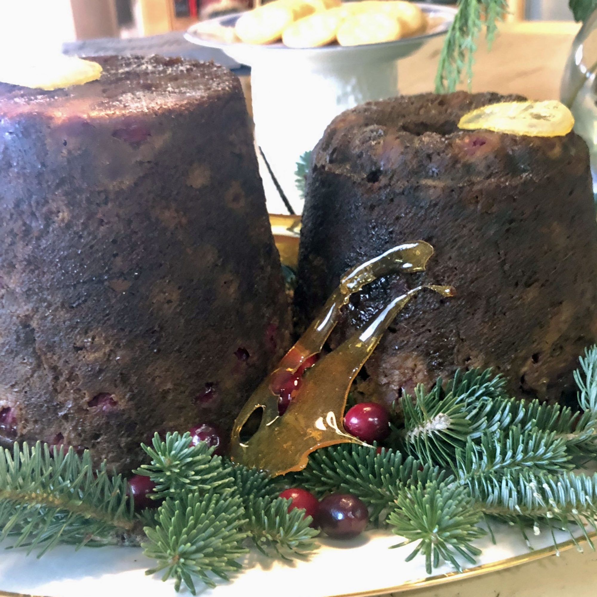 two Christmas puddings on a platter garnished with pine branches and decorative holly berries