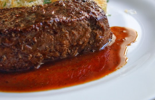 closeup of steak on a plate with a red wine reduction