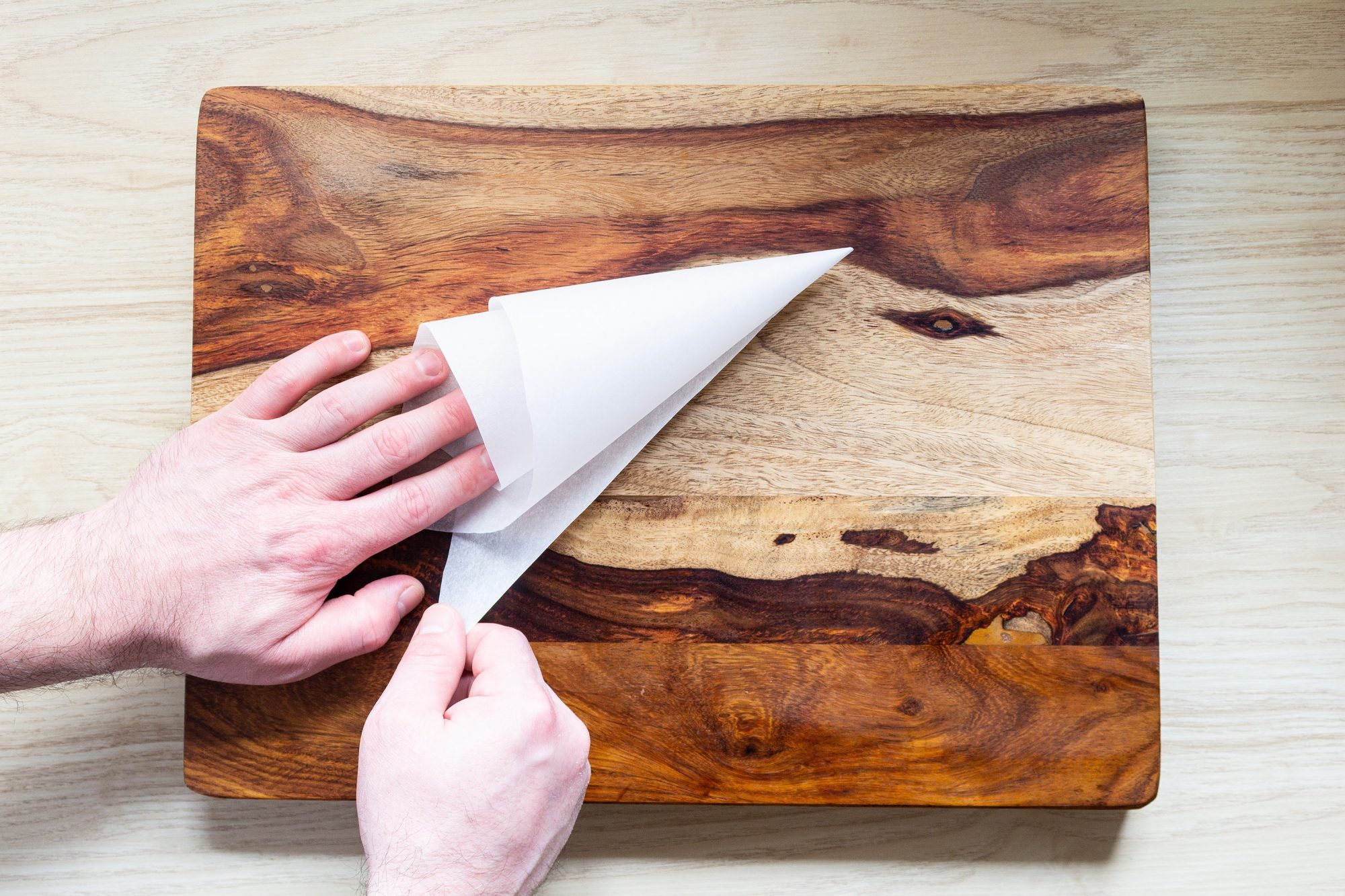 shaping a parchment paper triangle into a piping bag