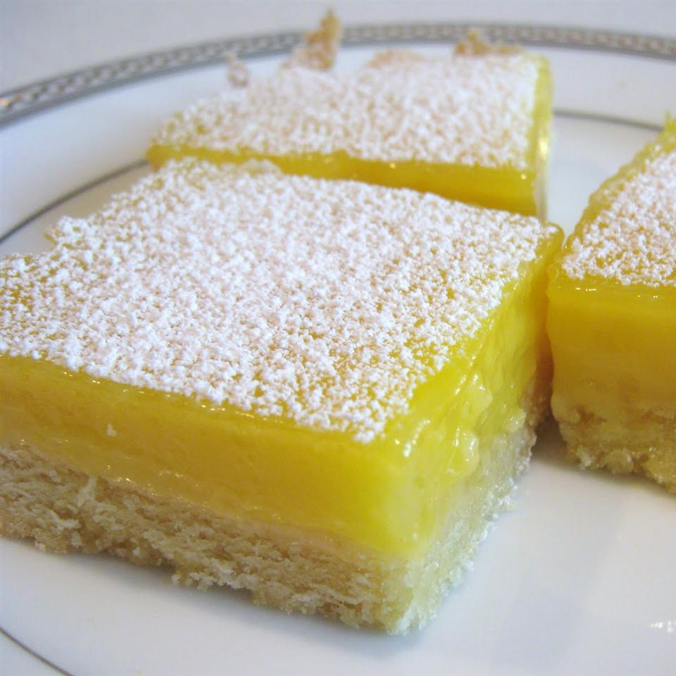 squares of lemon cream cheese bars sprinkled with powdered sugar
