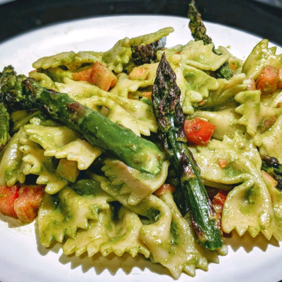 fusilli with asparagus and pesto on a white plate