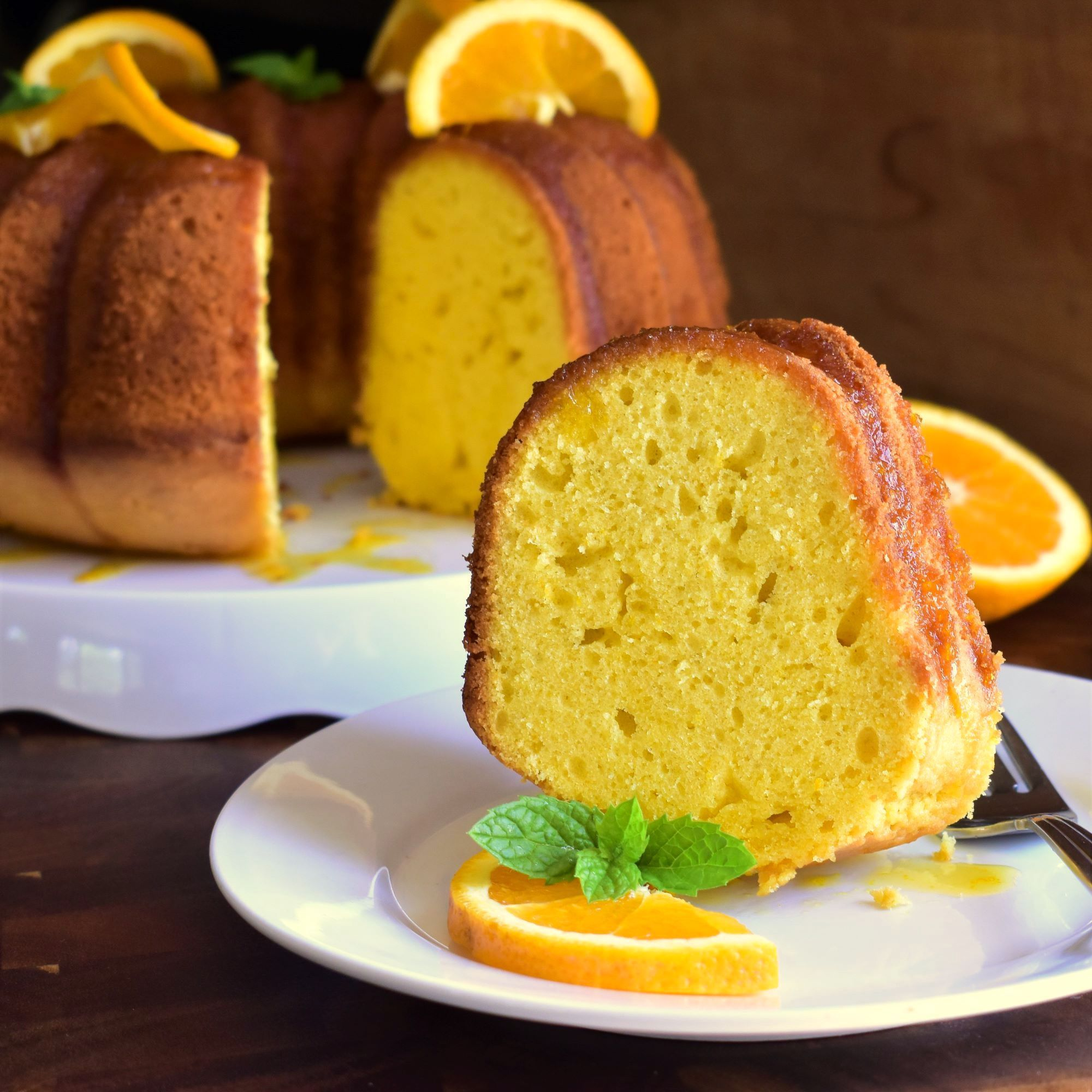 orange pound cake topped with orange slices on white plates