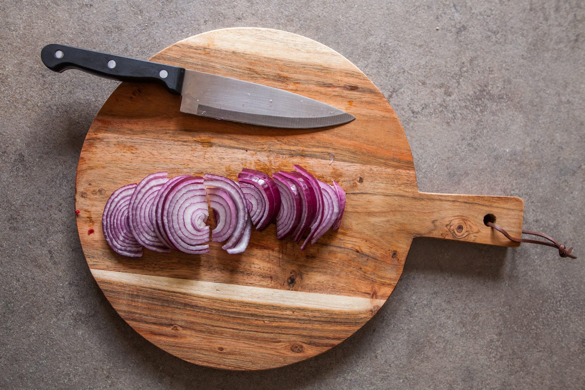 cutting board with a knife and slice red onion