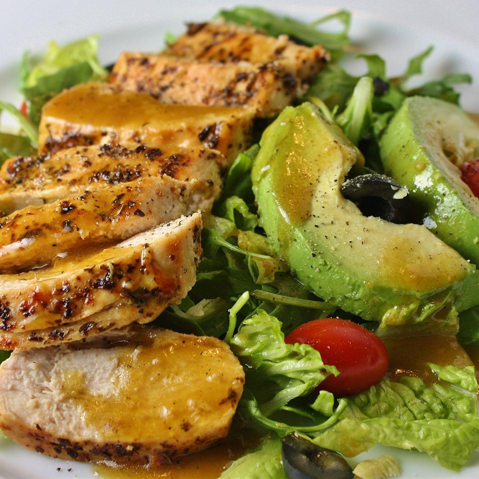 salad with grilled chicken, avocado, lettuce, tomatoes, and olives