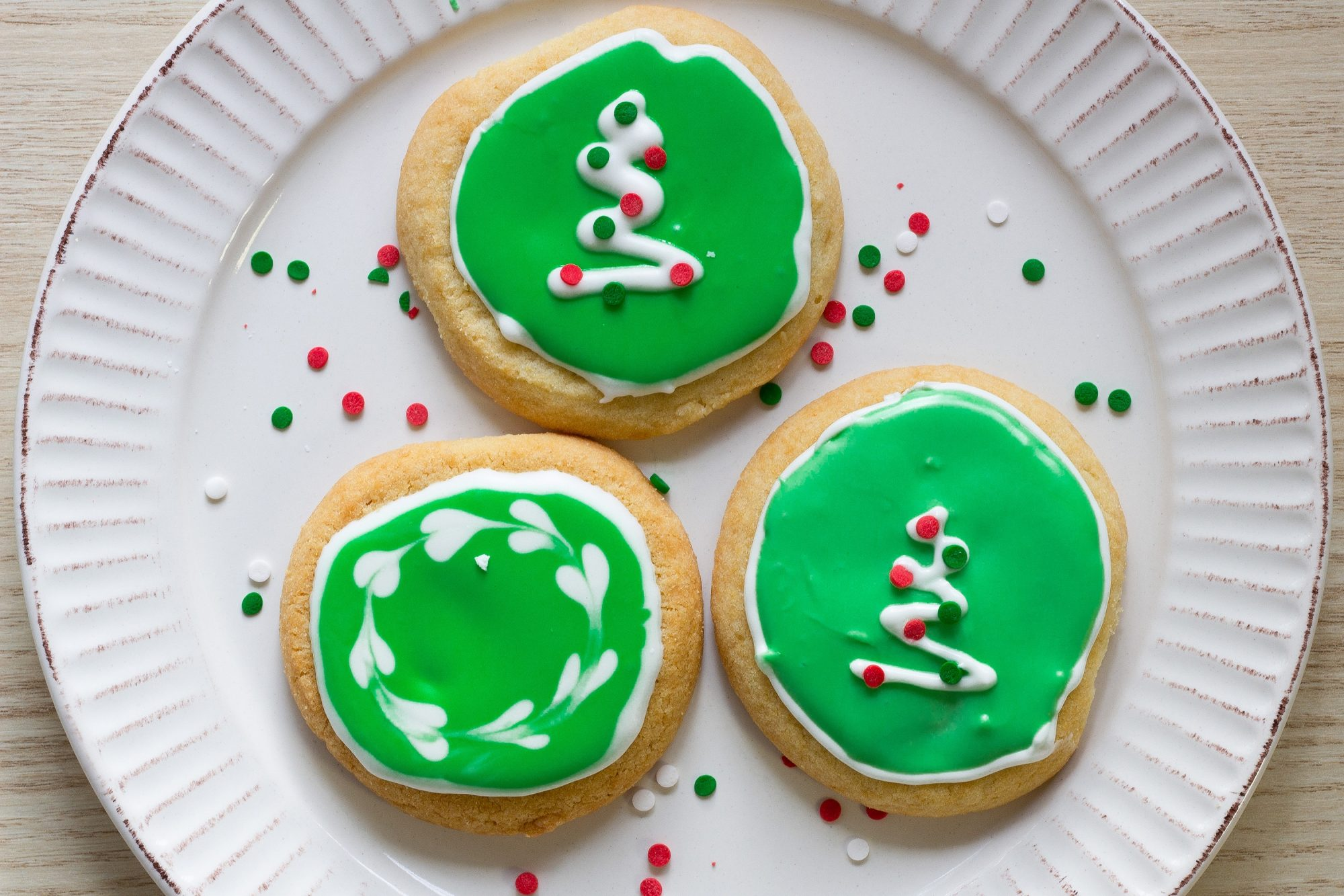 three sugar cookies decorated with green and white royal icing and green and red sprinkles