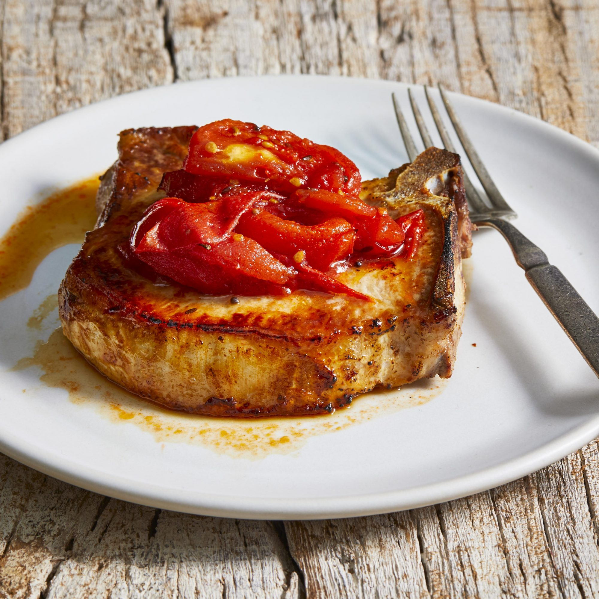 White plate with a pork chop covered in tomato chutney.