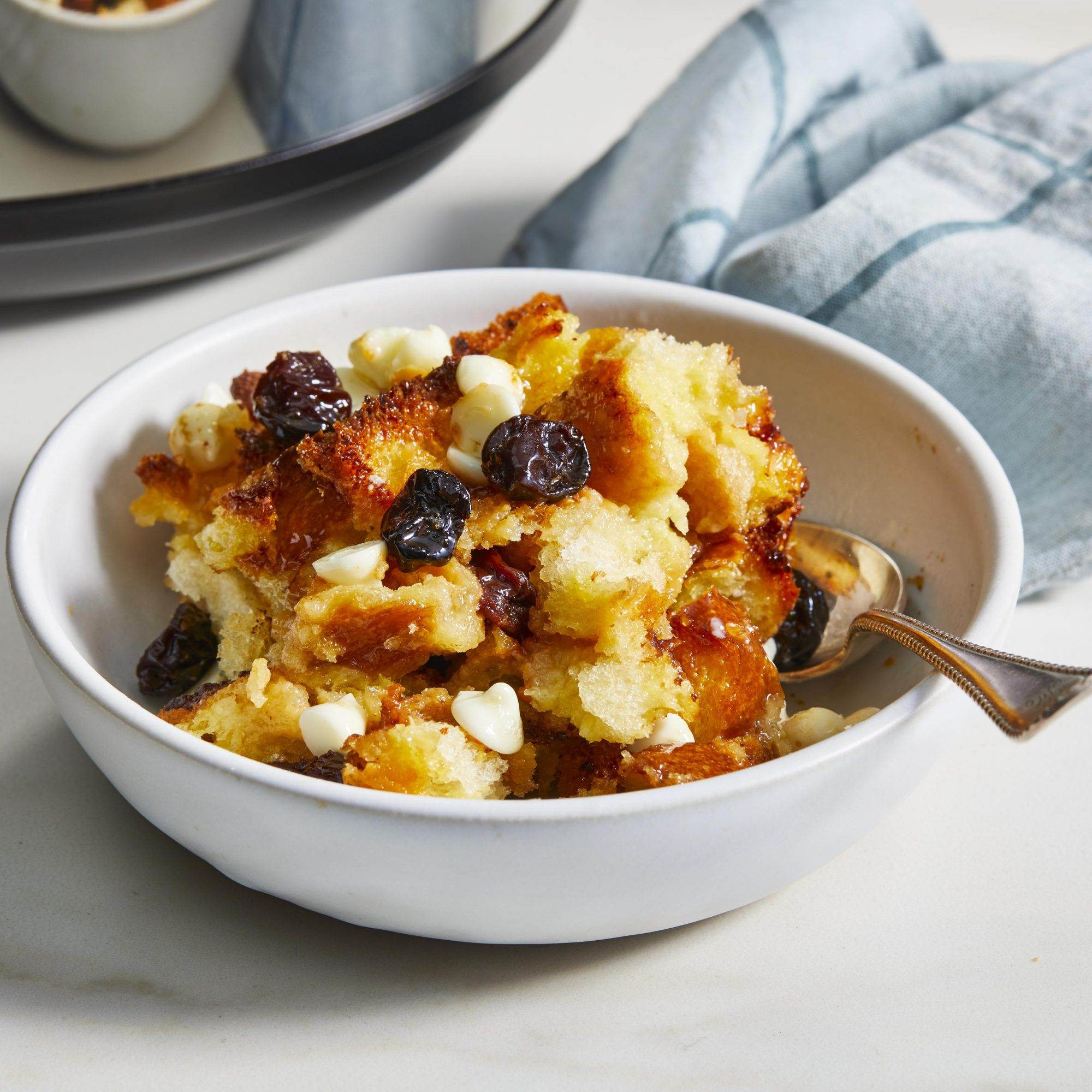 A bowl of bread pudding with a slow cooker in the background.