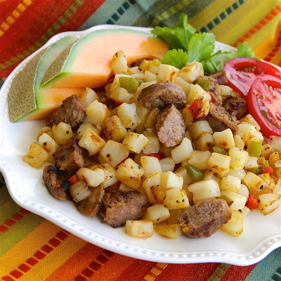 smoked sausage and potatoes with tomato slices and a slice of cantalope on a plate