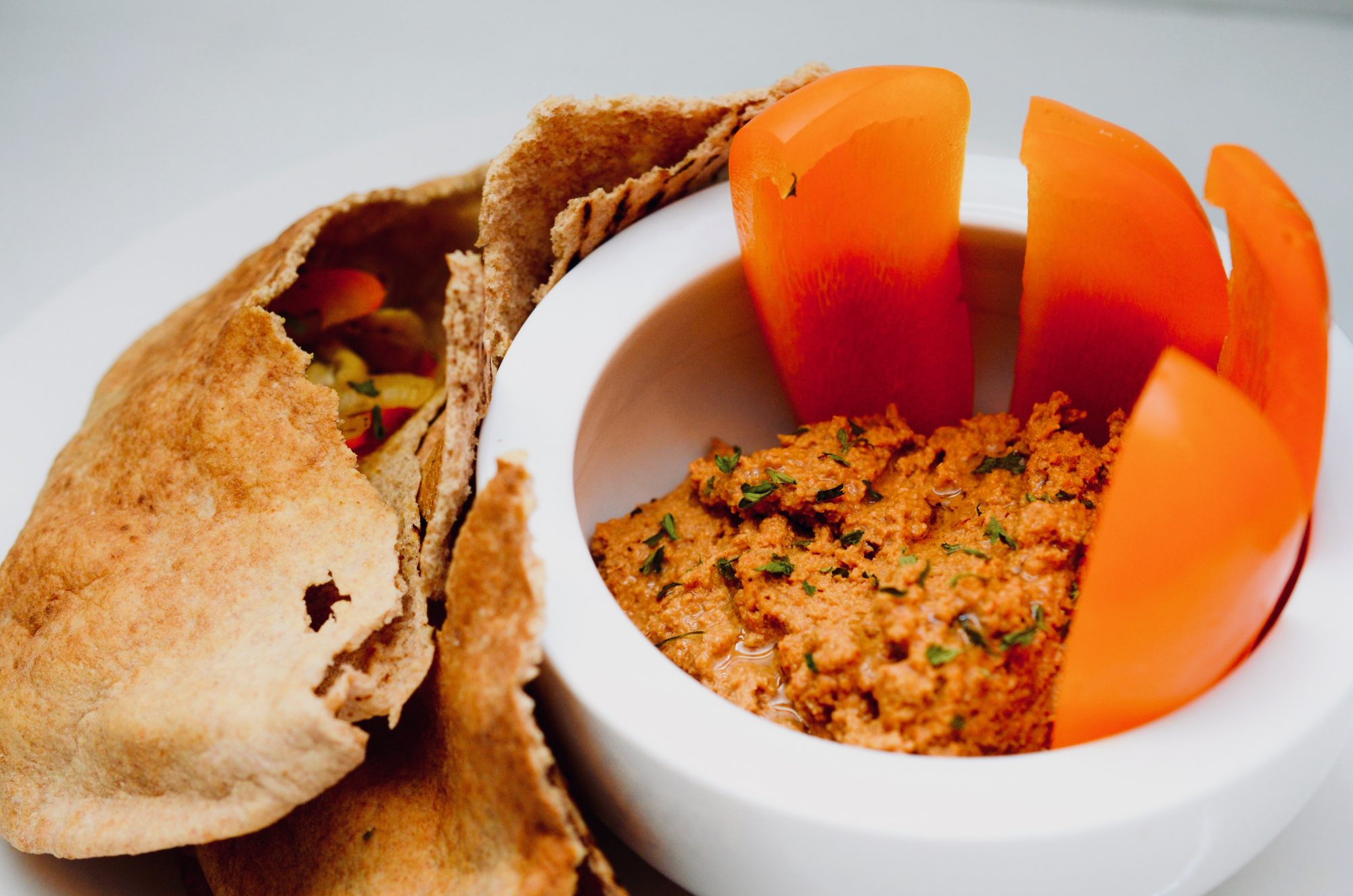 red pepper and walnut spread with pepper and bread accompaniments