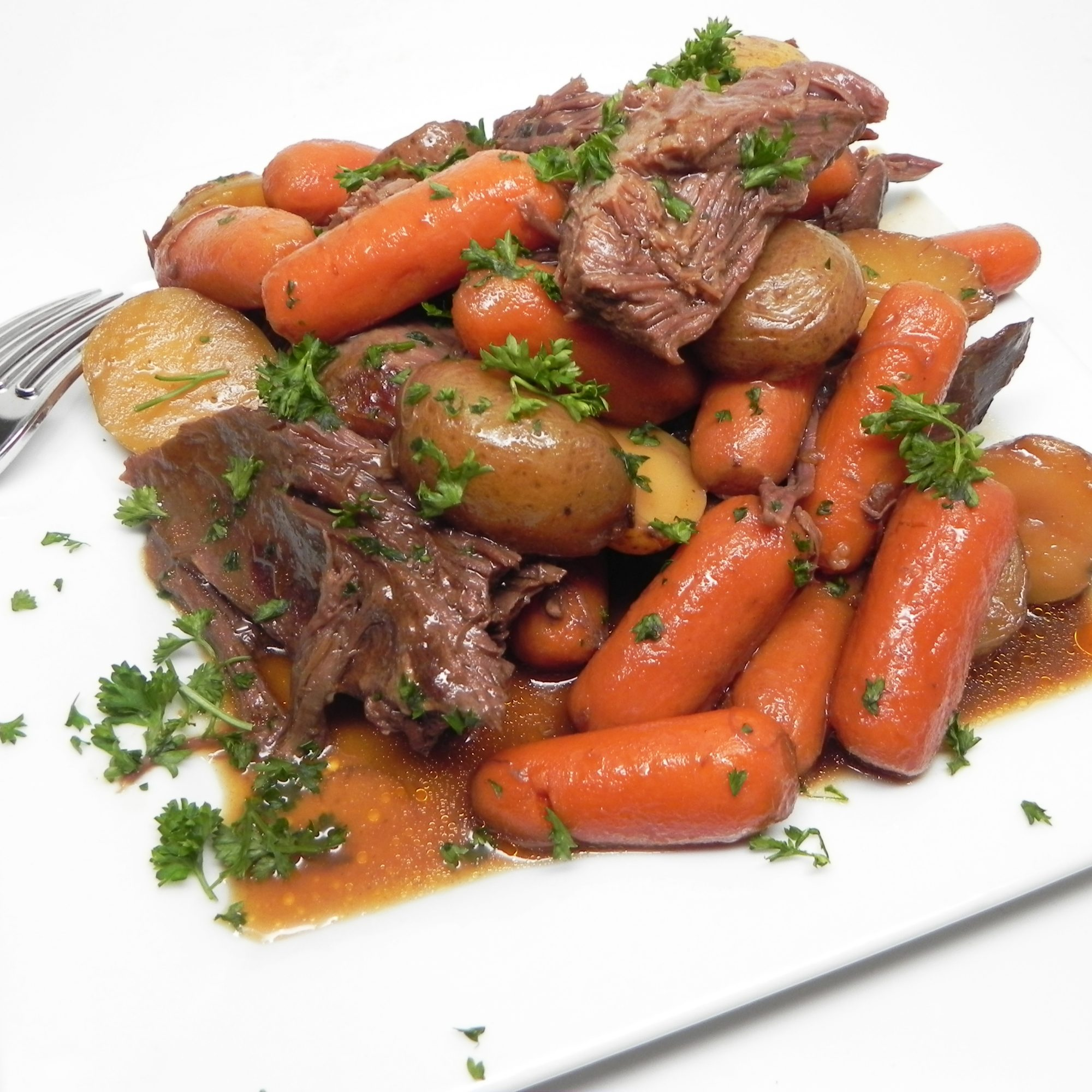 Instant Pot Venison Pot Roast with carrots and potatoes and meat on a white plate