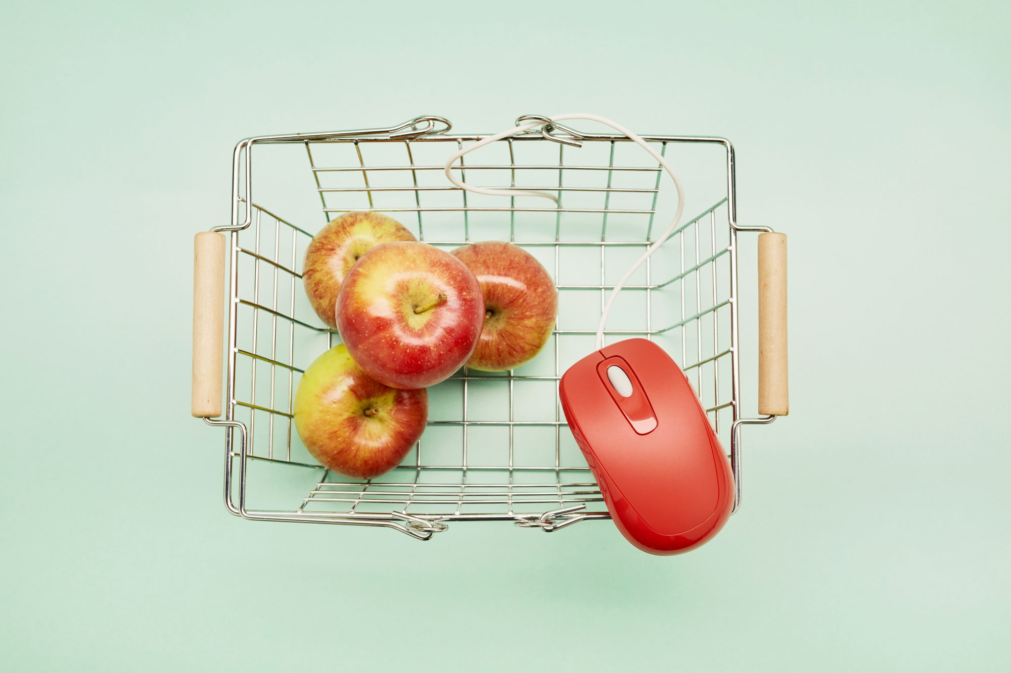 Directly above shot of a shopping basket, apples and red computer mouse on turquoise background