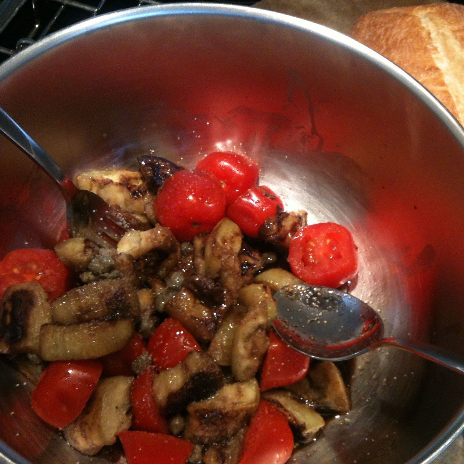 eggplant and tomatoes in a stainless steel bowl