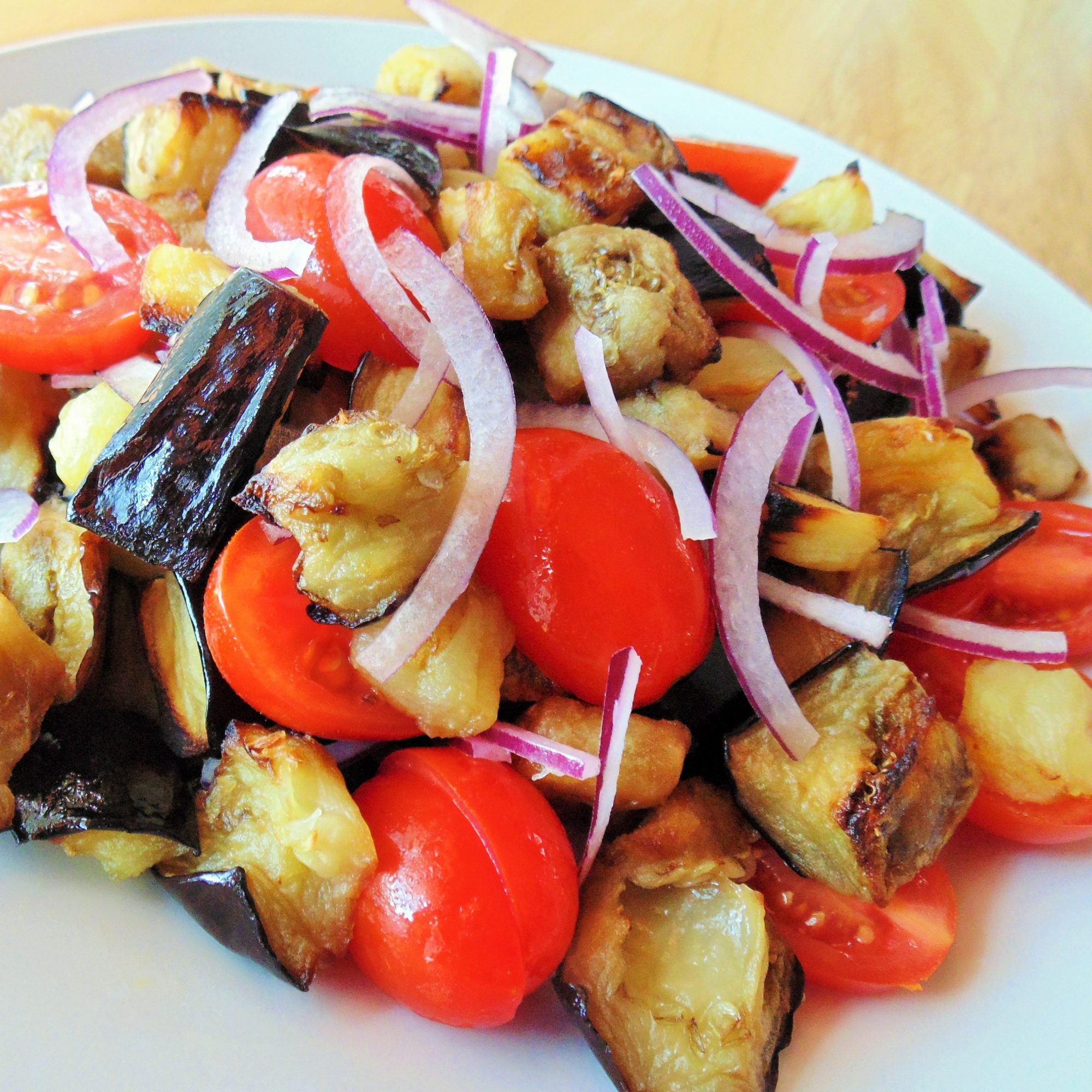 eggplant and tomato salad on a white plate