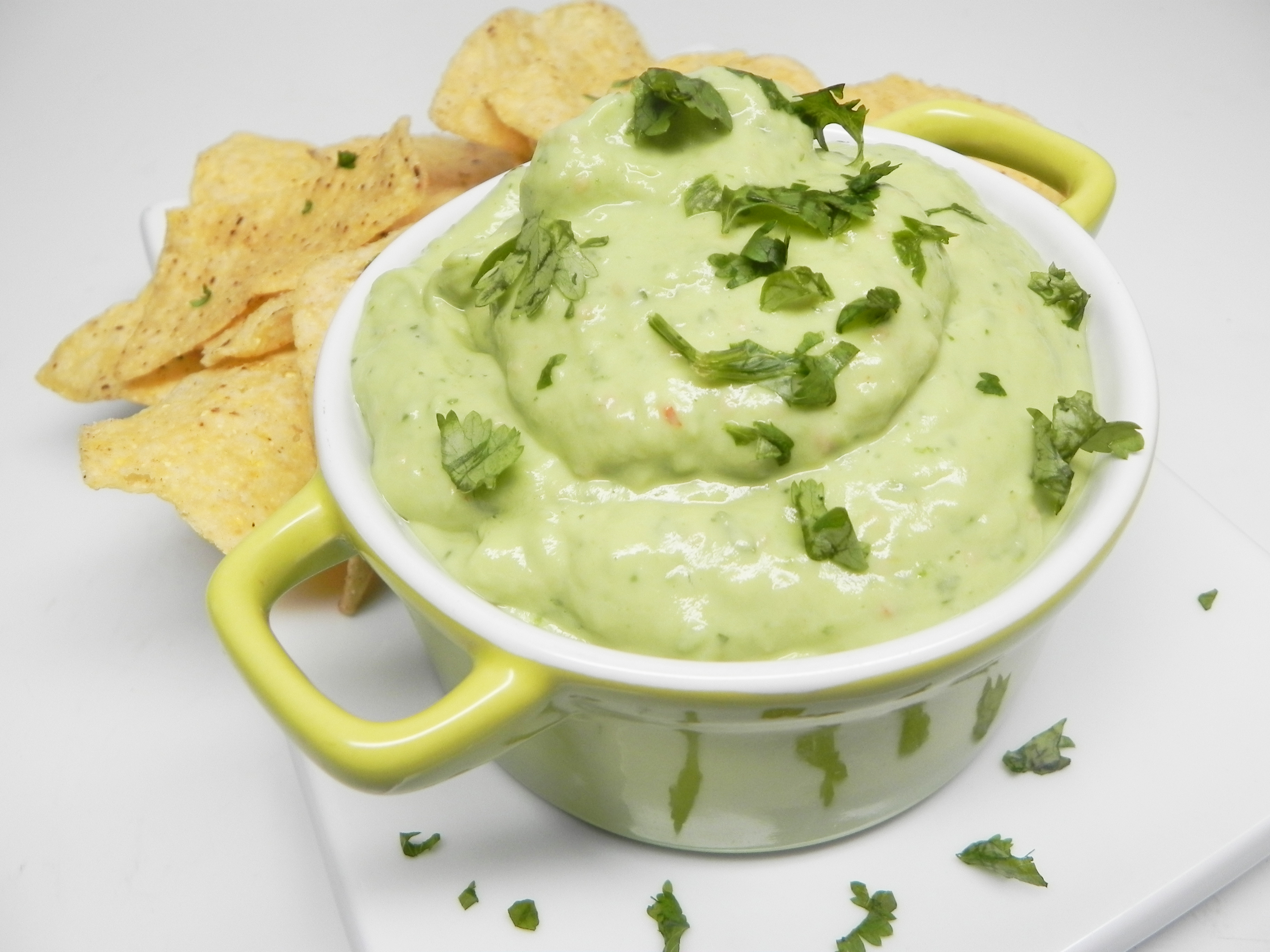 creamy avocado sauce in a green serving dish with tortilla chips