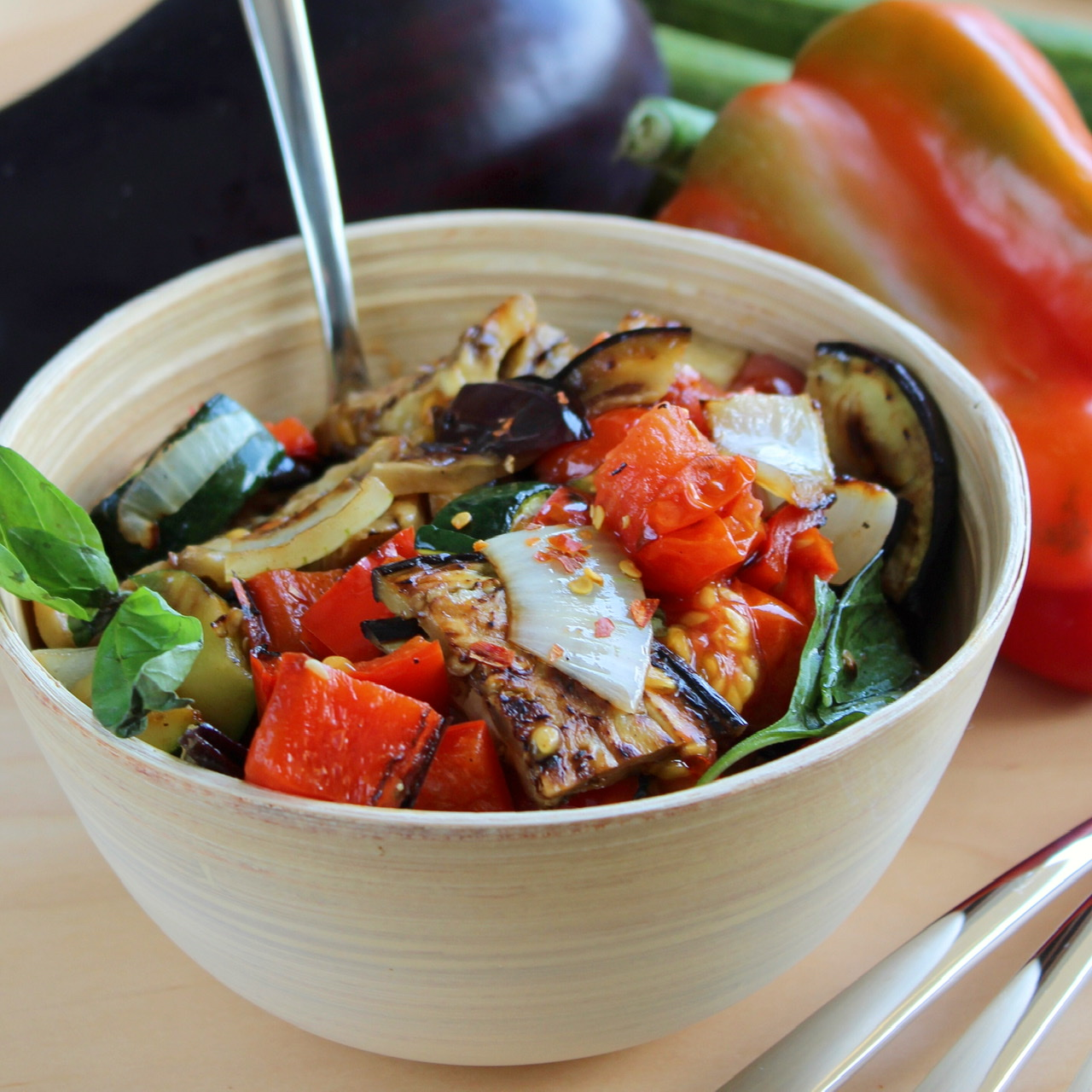 grilled eggplant, bell pepper, zucchini, tomatoes, onions, and basil in a bowl