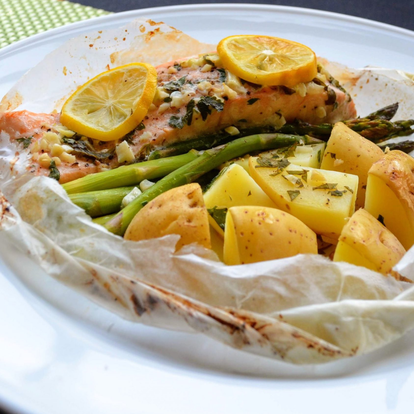 salmon, potatoes, and asparagus in parchment paper on a white plate