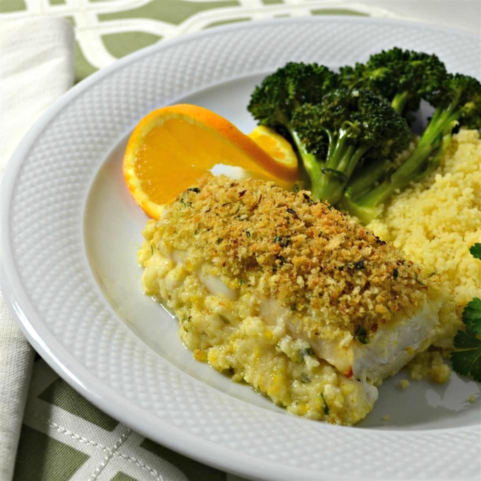 filet of citrus crusted haddock with an orange garnish and sides of couscous and broccoli