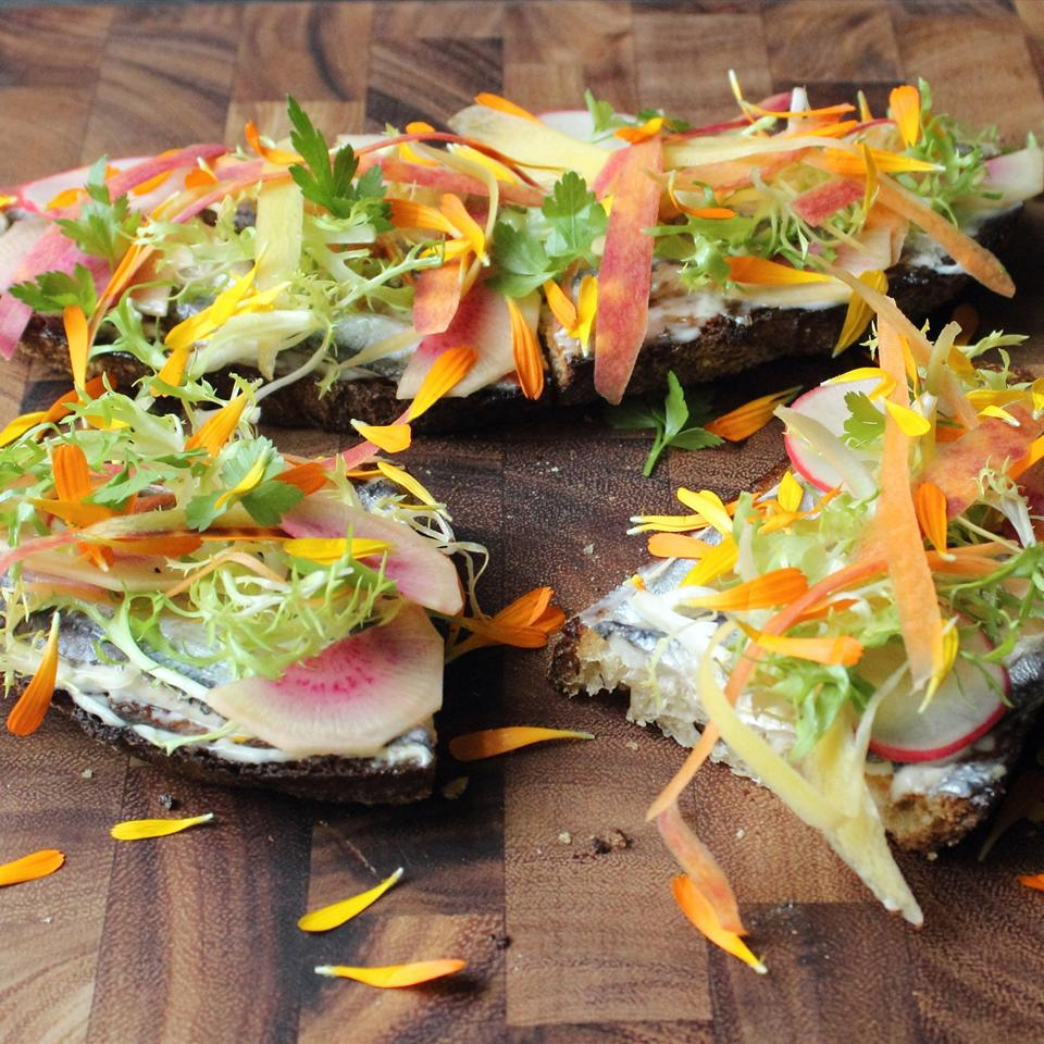 vegetables and white anchovies on brown bread