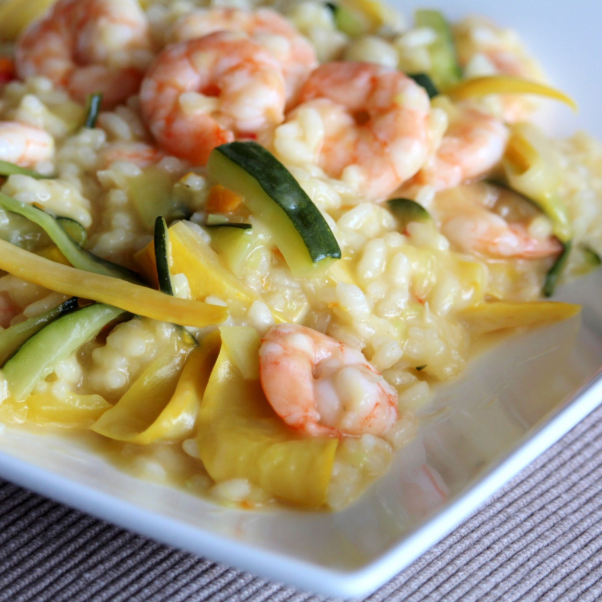 risotto with shrimp, asparagus, squash on a white plate