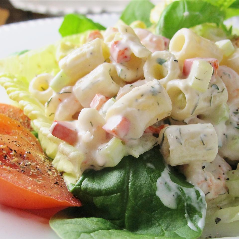 macaroni salad with shrimp and eggs over lettuce and sliced tomato on a white plate