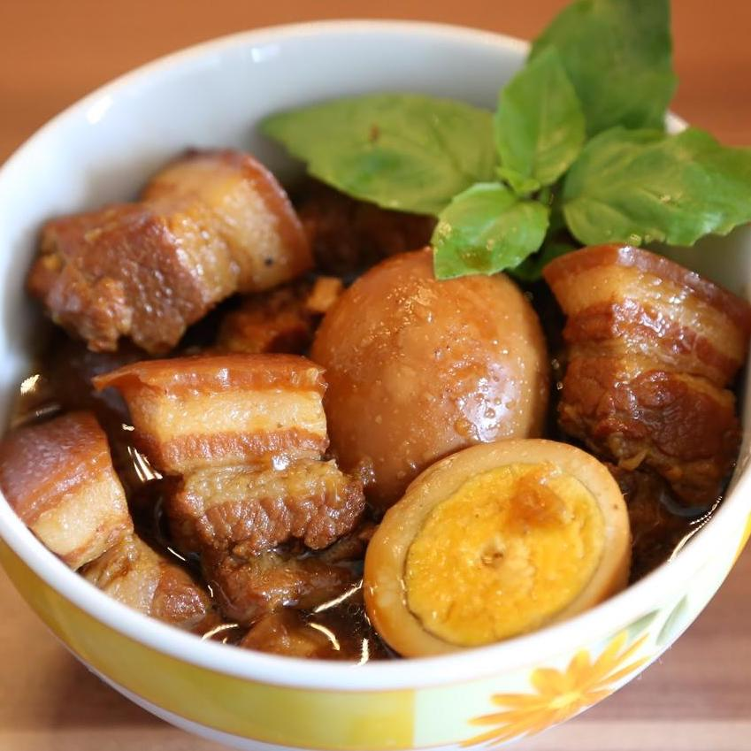 bowl of caramelized pork belly with egg halves in broth