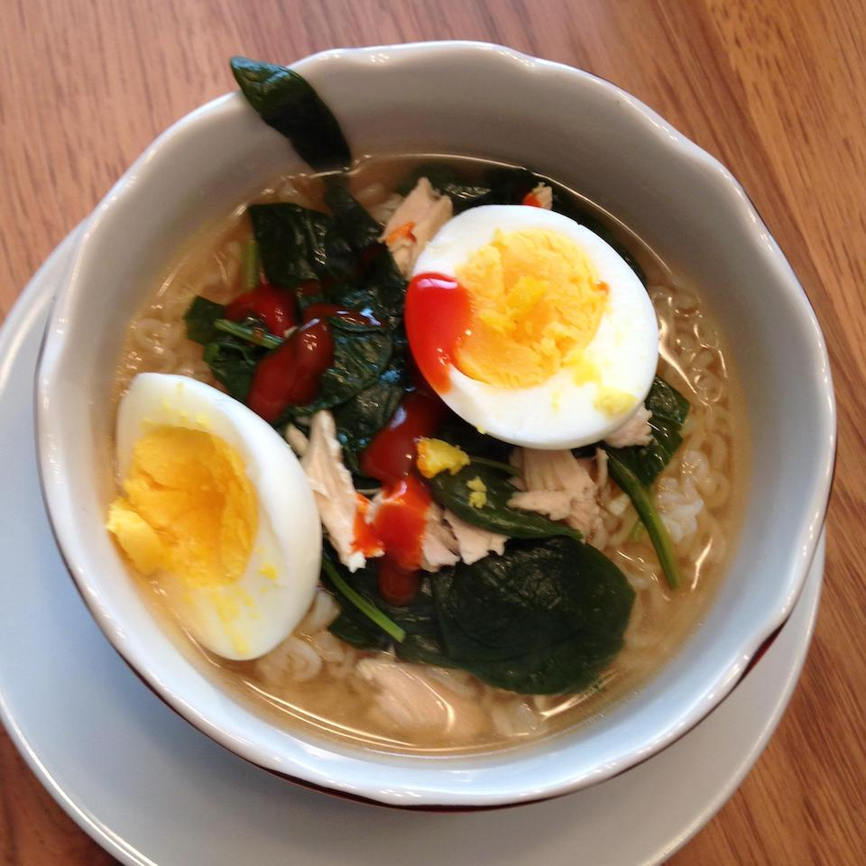 bowl of chicken and ramen noodle soup topped with eggs