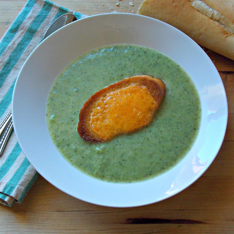 top-down view of a bowl of creamy broccoli soup topped with a baguette slice covered with melted cheddar