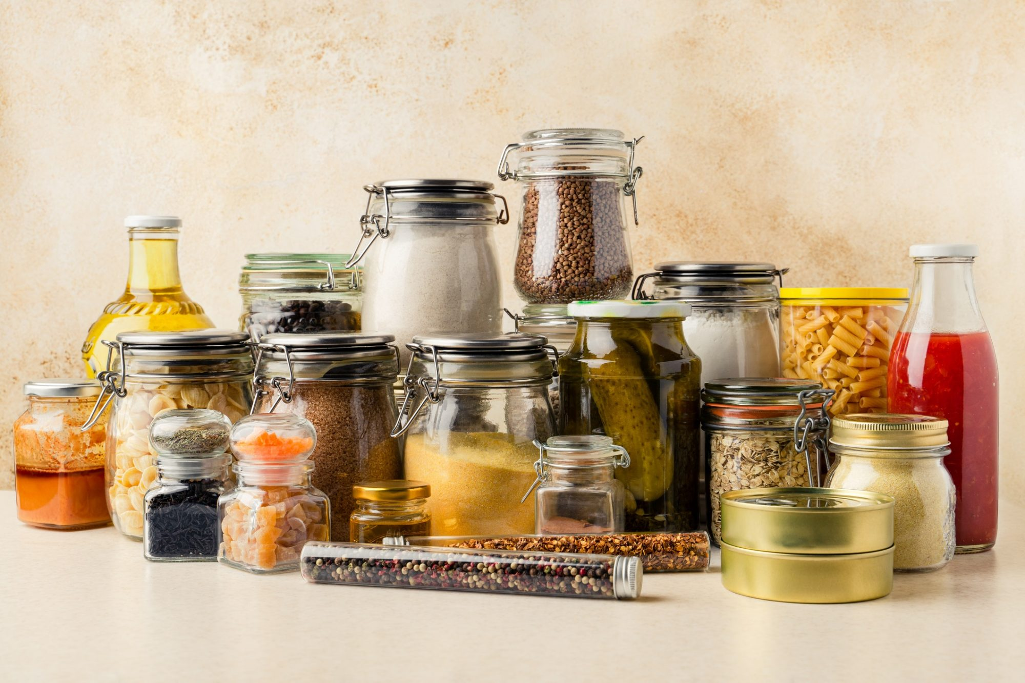 Various pantry ingredients including grains, condiments, tomato sauce, oil in glass containers, canned produce