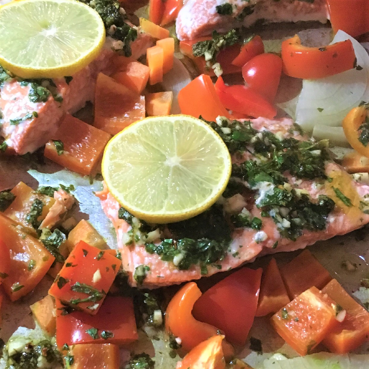A complete dinner on a sheet pan, with salmon, bell peppers, garlic, lemon, and herbs