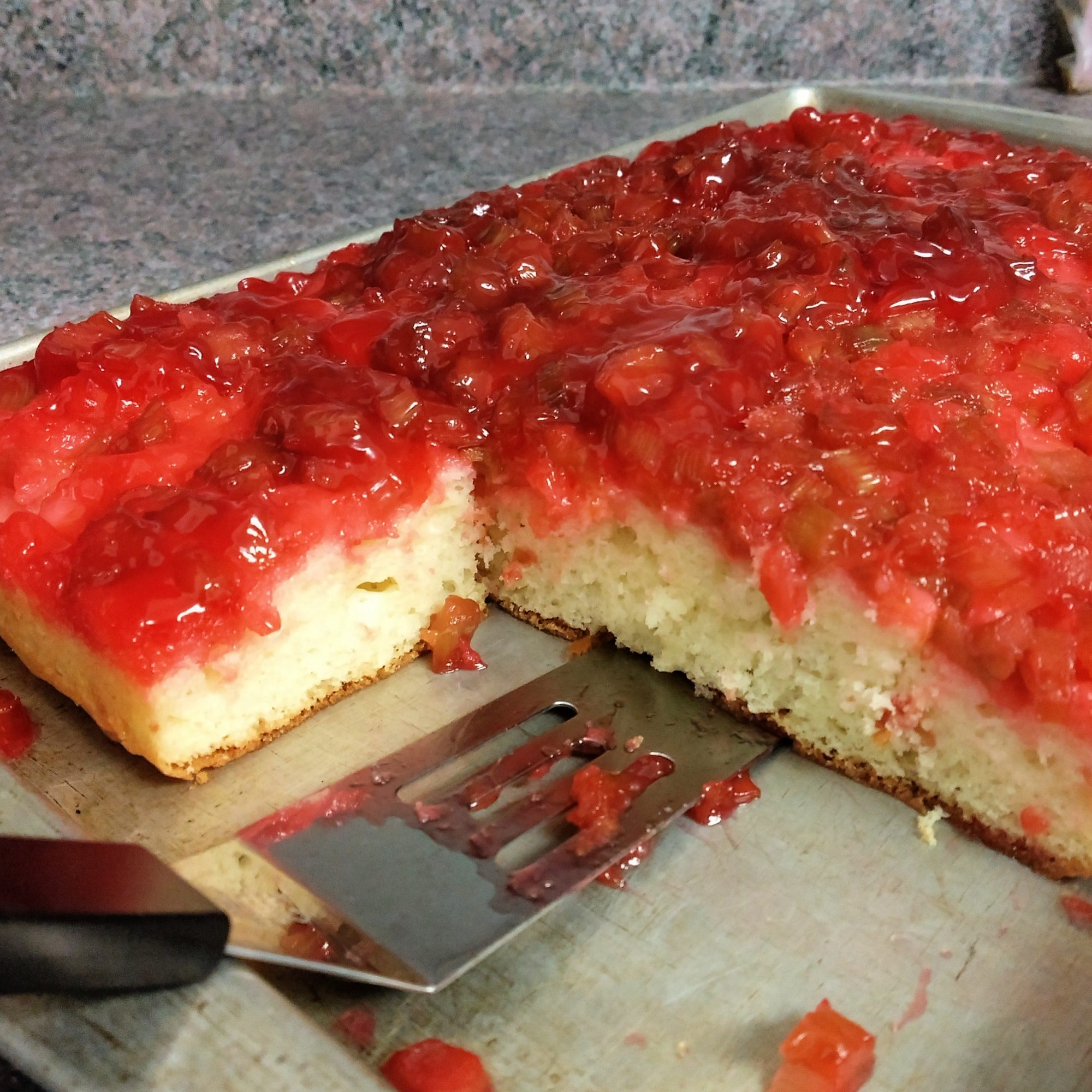 side view of upside down rhubarb cake in a baking pan