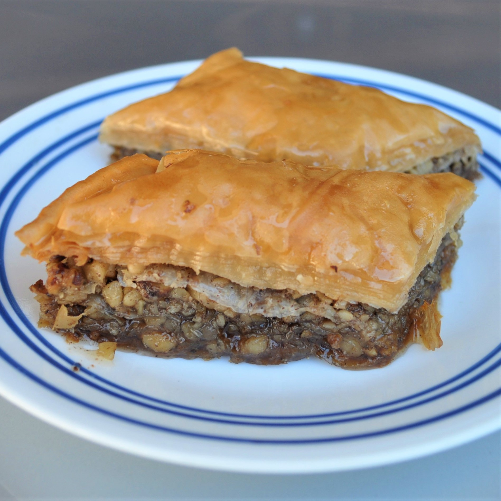 Two slices of baklava on a blue and white plate