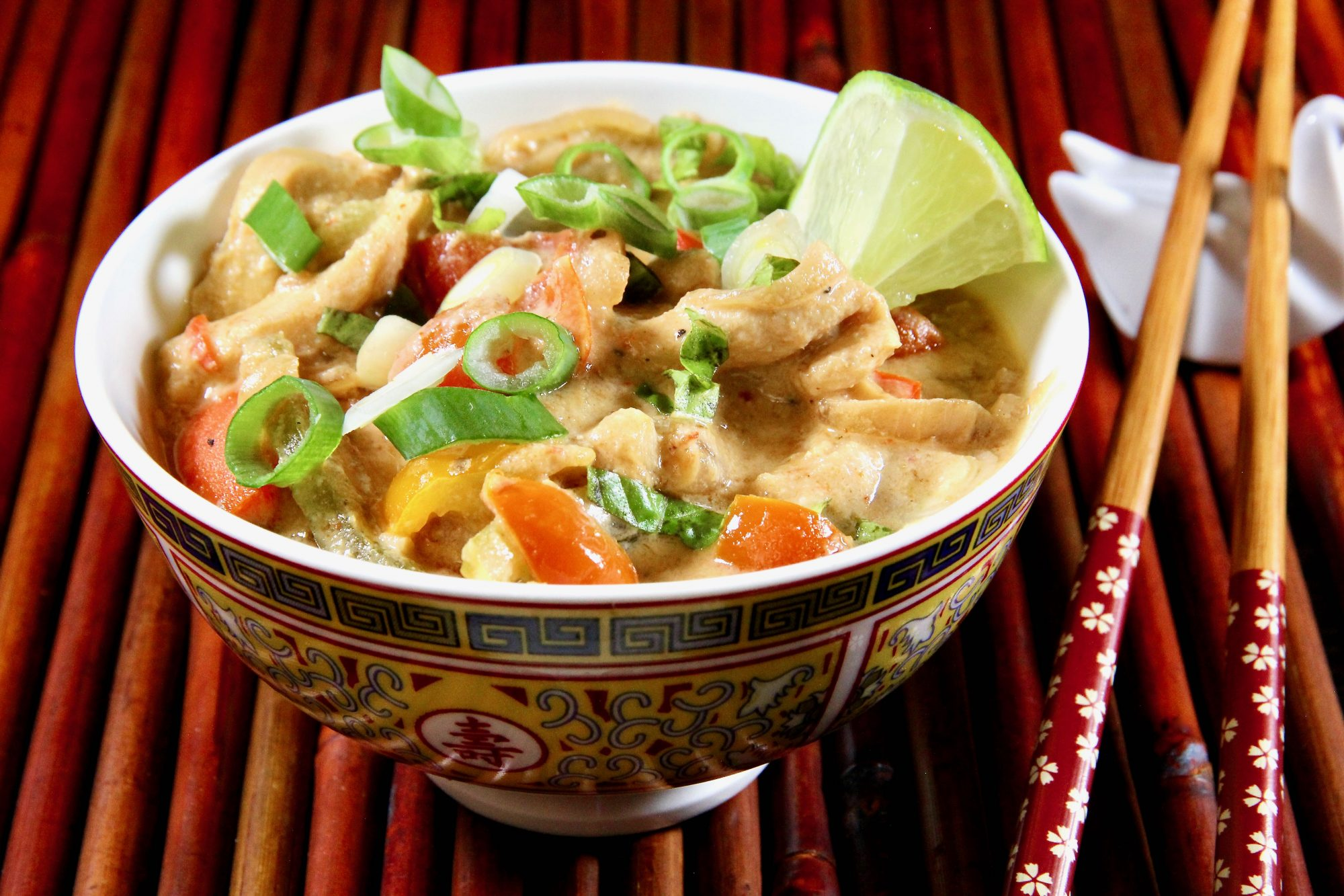 a small bowl filled with chicken breast strips, red bell pepper, and coconut milk garnished with sliced scallions and a lime wedge