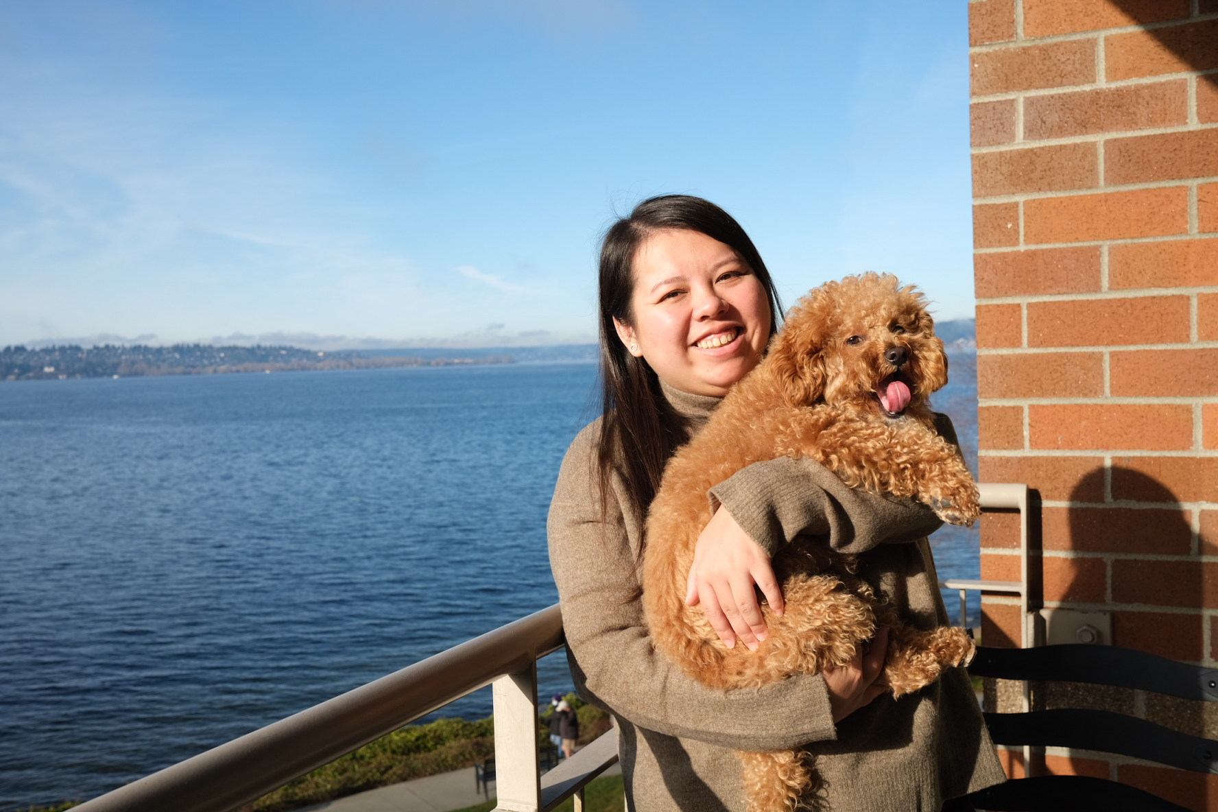 Annie Nguyen and Mochi - a woman holds her brown dog and smiles