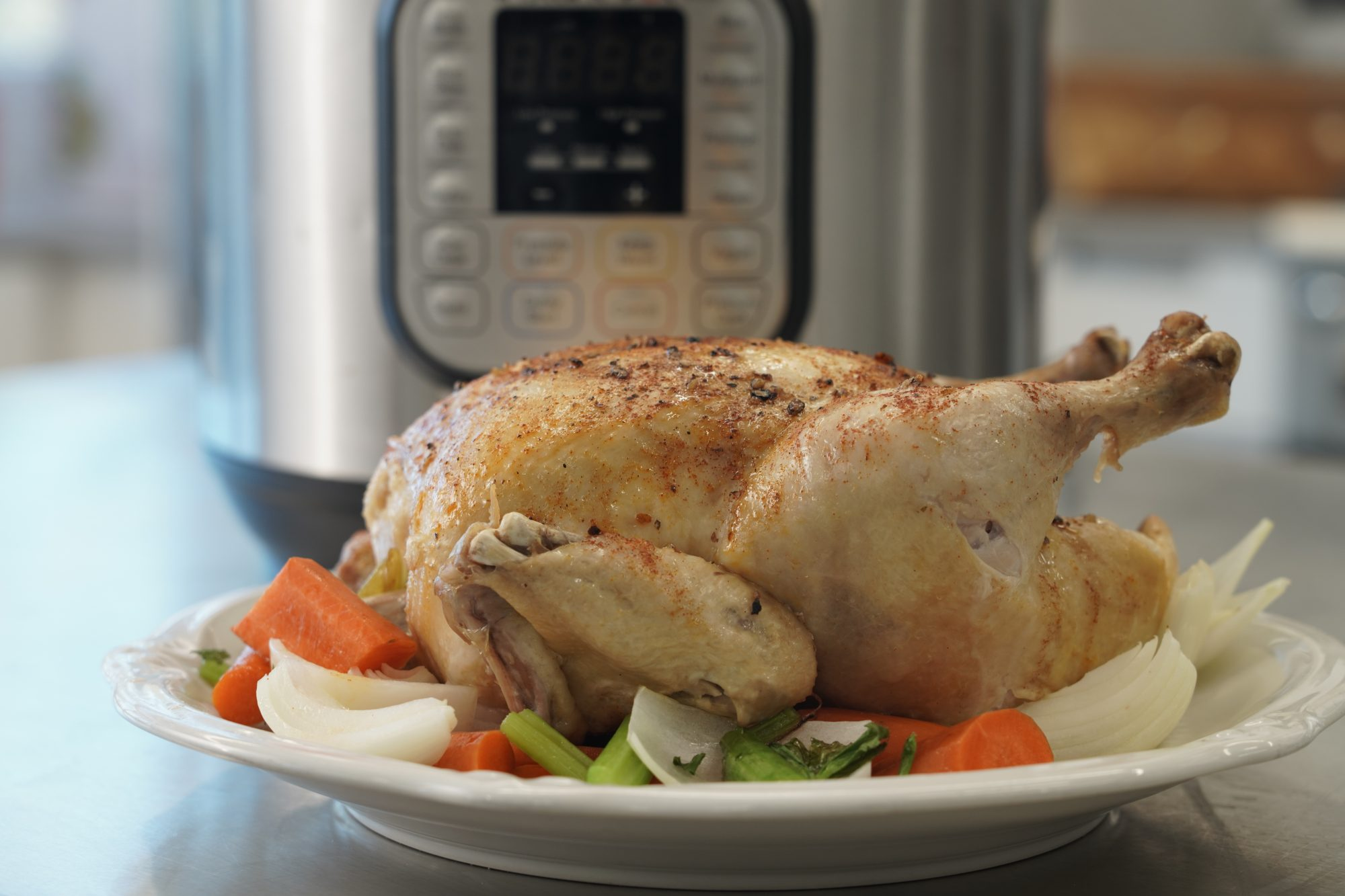 whole chicken cooked in an Instant Pot on a bed of vegetables