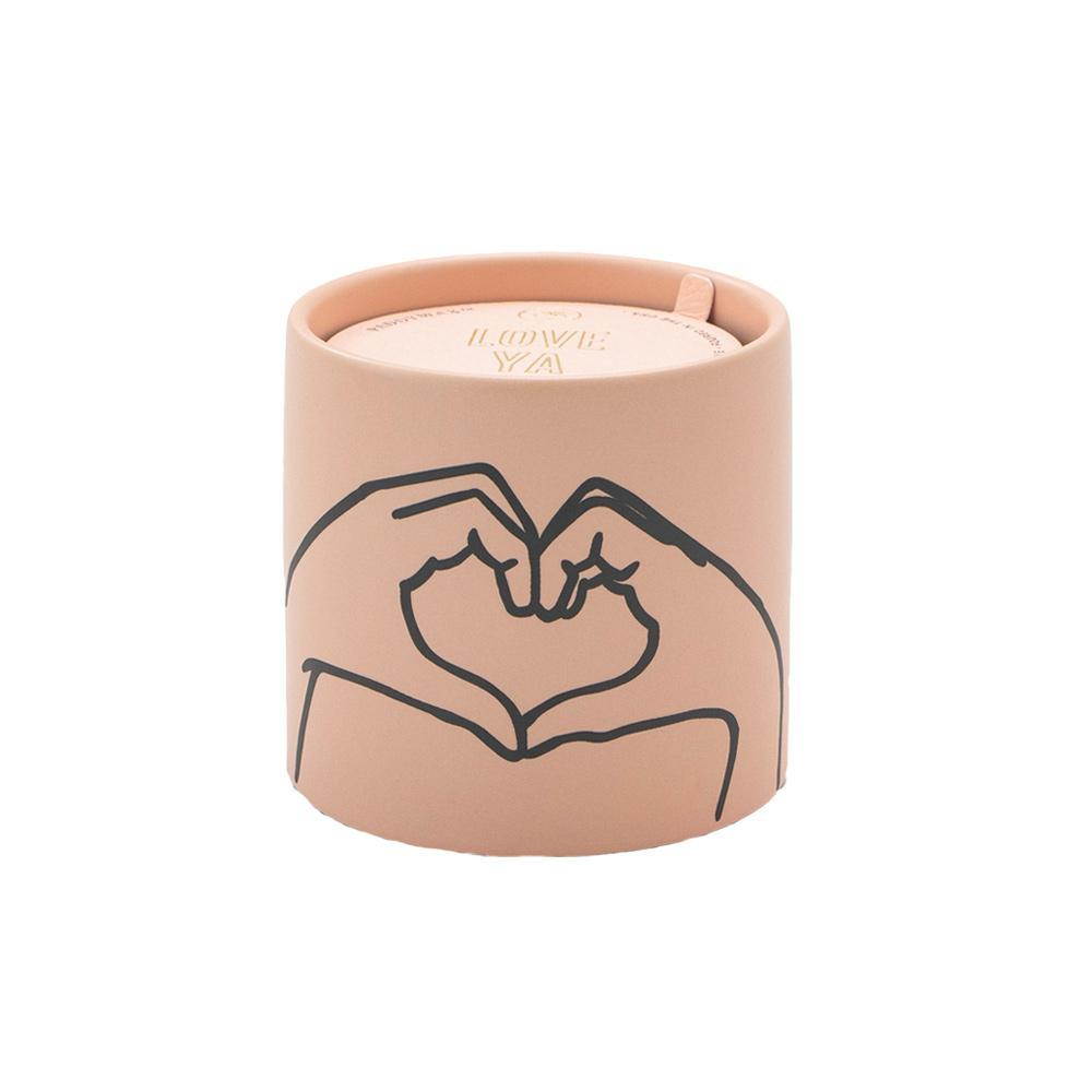 pink candle with illustration of hands forming a heart
