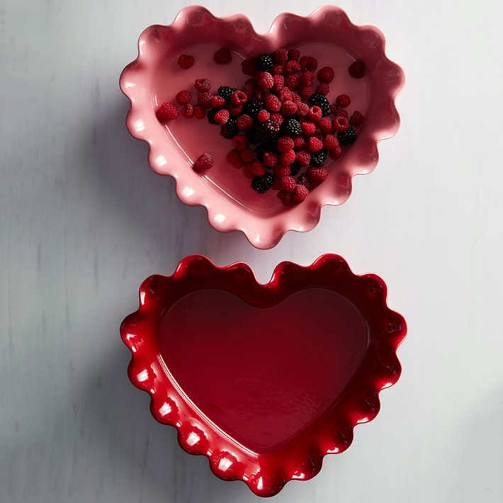 Pink and red heart-shaped pie dishes with berries