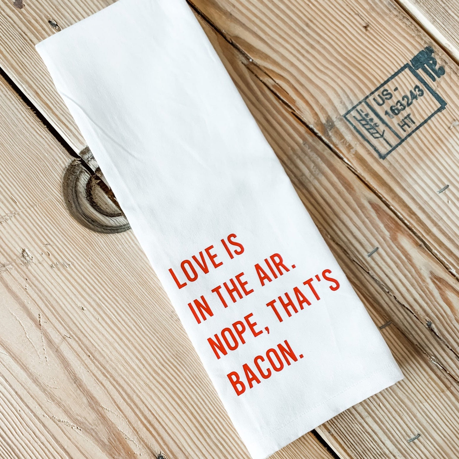 "white tea towel that reads ""Love is in the air. Nope, that's bacon."" in red print"