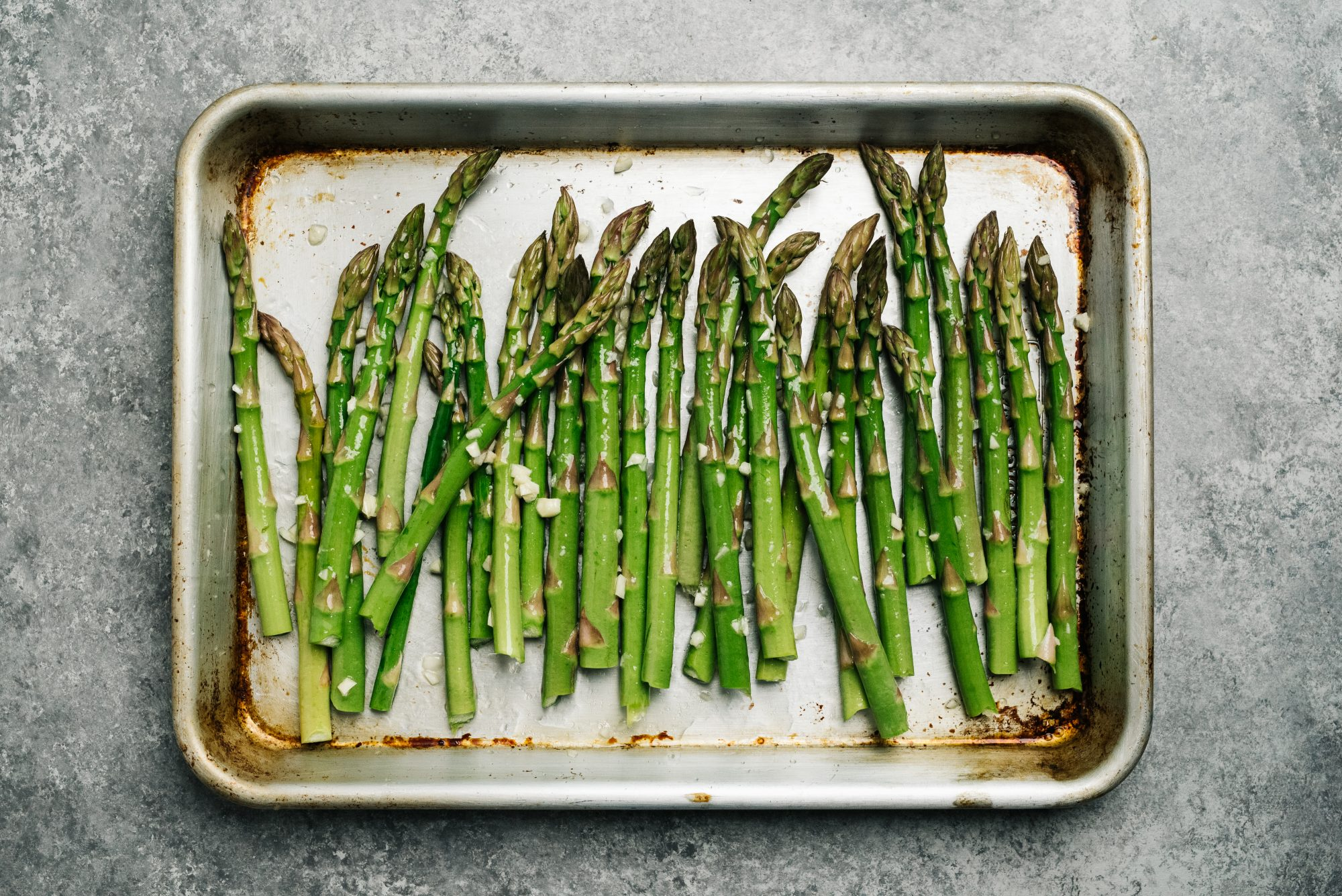 Oiled asparagus on a quarter sheet pan