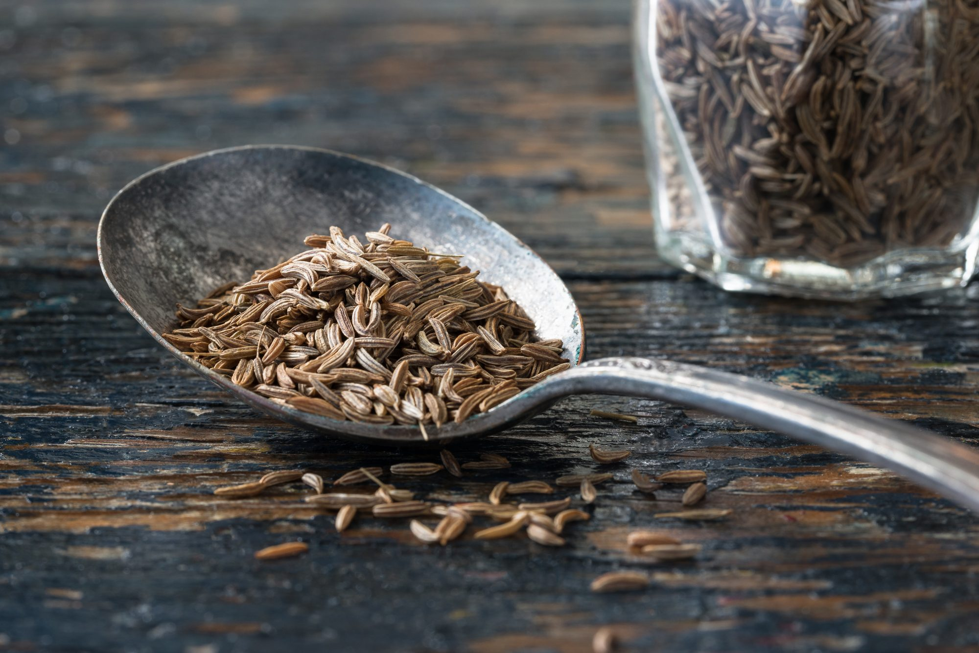 Close-Up Of Caraway Seeds In Old Spoon On Wooden Table