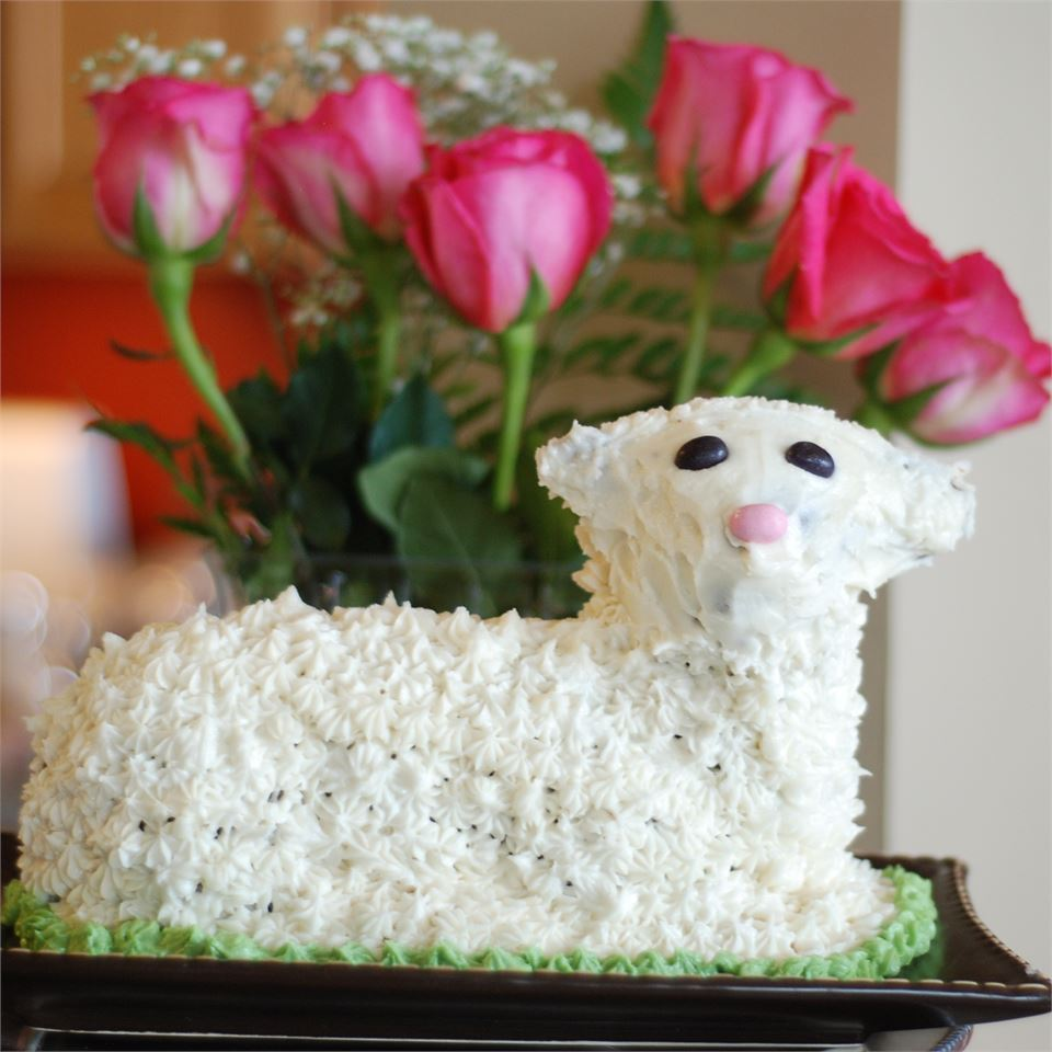 lamb cake with piped icing on platter in front of flowers